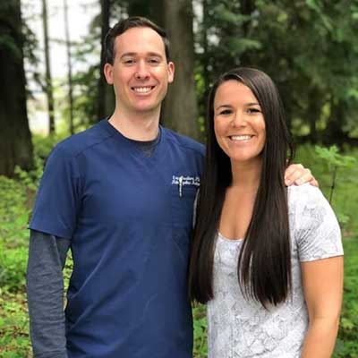 Emily and Eric, Co-Owners of Nearing Total Health, pictured standing in front of a green forest